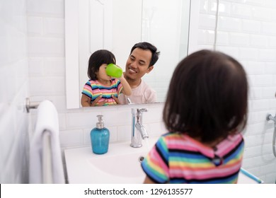 little girl gargle after brush her teeth with dad in the bathroom sink at home
