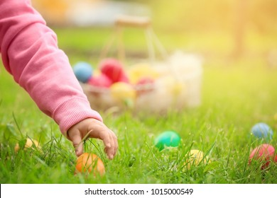 Little girl gathering colorful egg in park. Easter hunt concept