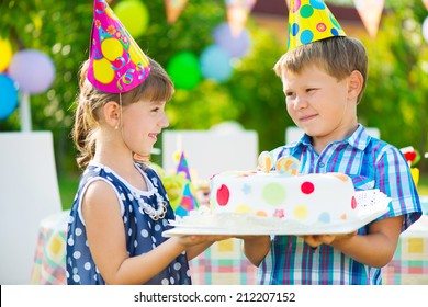 Little girl giving a birthday cake to her friend