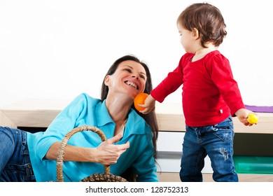 Little girl giving her mother an orange