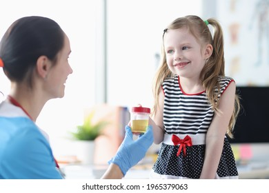 Little girl giving jar of urine to nurse in clinic
