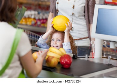 Little girl giving muskmelon to female cashier at counter for billing in supermarket