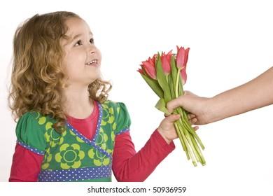 Little girl giving a tulip bouquet
