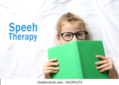 Little girl in glasses with book on bed. Text SPEECH THERAPY on background