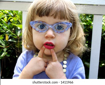 Little girl with glasses, lipstick, necklace and expression playing dress-up