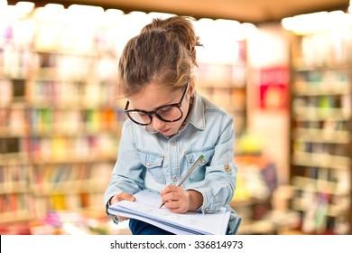 Little girl with glasses studing on unfocused background