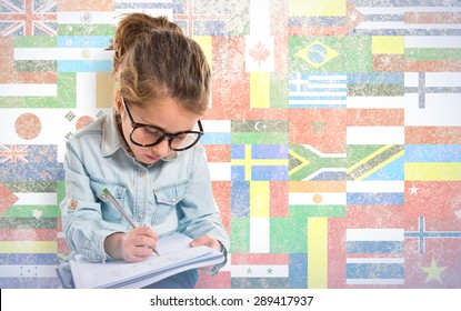 Little girl with glasses studing over flags background