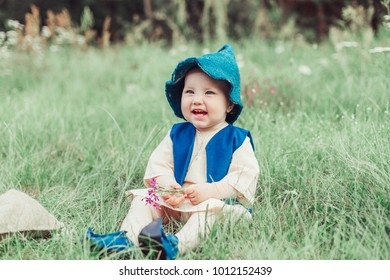 Little girl in a gnome hat sitting on a green grass in a green forest in the summer have a nice day. Childhood, nature and happiness concept