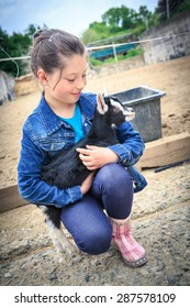 little girl with a goat kid in front of the farm