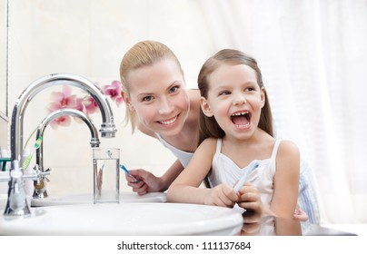 Little girl is going to brush her teeth with her mother