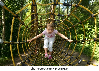 little girl going trough tunnel in forest attraction park