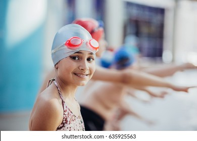 Little girl in googles swim in pool