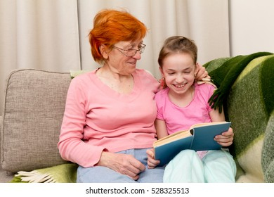 little girl with grandma having fun sitting on sofa and reading book together