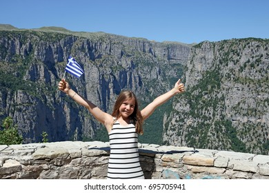 little girl with a Greek flag and thumb up on Vikos gorge Zagoria Greece
