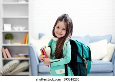 Bambina con zaino verde in possesso di cancelleria in soggiorno