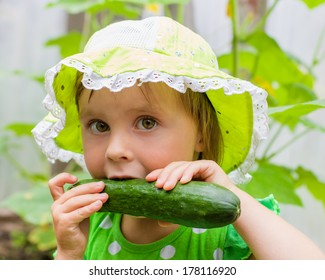 Little girl in a green hat, eating fresh cucumber from the garden