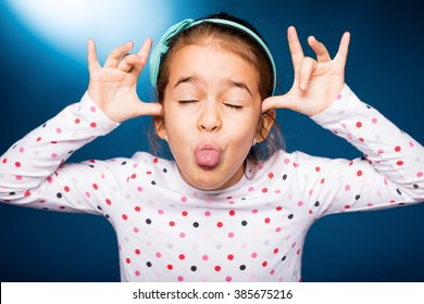 little girl with green headband with bow, pull faces