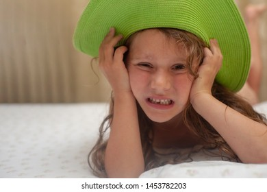 The little girl in green sun hat without a first baby tooth.