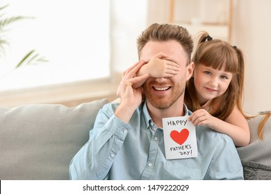 Little girl greeting her dad with Father's Day at home