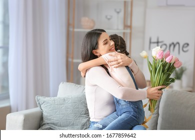 Little girl greeting her mom with Mother's Day at home