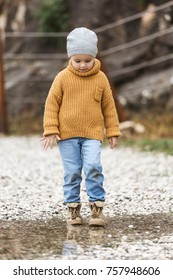 Little girl with grey hat, orange sweater, dirty jeans and boots steps in puddle with splashing. Time autumn or winter.