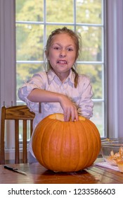 A little girl grimaces at the slimy texture inside her Halloween pumpkin.