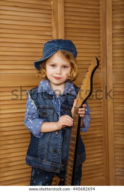 little girl with a guitar in a denim jacket dreams of becoming a pop star