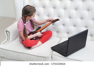 Little girl with guitar looks at laptop. Online education.
