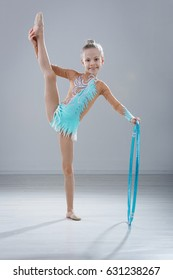 little girl gymnast in blue dress with hula hoop in the  studio gray background