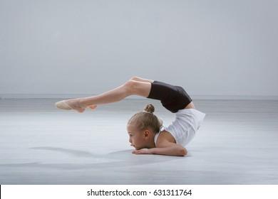 little girl gymnast in studio gray background