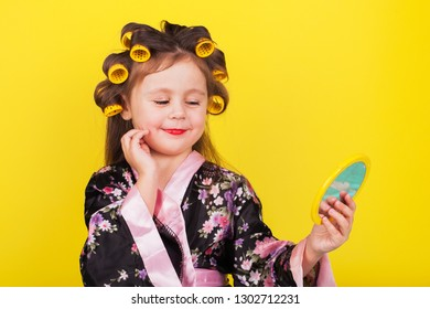 little girl in hair curlers looks in the mirror