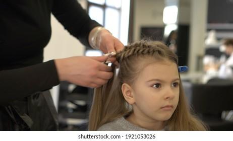 Little girl in hair salon, hair braiding.