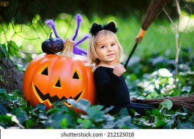 little girl in halloween costume eat sweet tricks with jack pumpkin