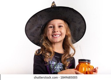 little girl in halloween costume holding a pumpkin in her hands on a white background
