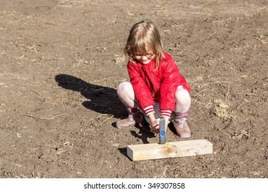 little girl hammers a nail into a plank