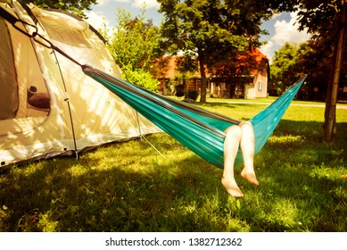 Little girl in the hammock and the tent in background in the sunny summer day. Summertime and vacation concept.