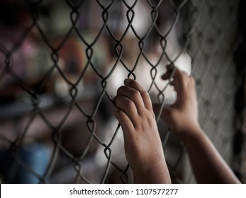little girl hand holding on chain link fence for freedom, Human Rights Day, child labor, violence concept.