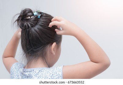 little girl hand itchy scalp on gray background, Hair care concept