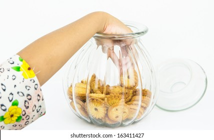 Little girl hand taking cookies from a jar.