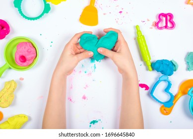 Little girl hands close up playing with colorful modeling clay on white background. Home Education game with clay. Child sculpting heart figure from clay. Top view. Early development concept