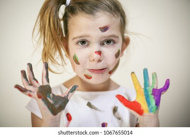 Little girl with hands and face covered with paint. Space for copy.
