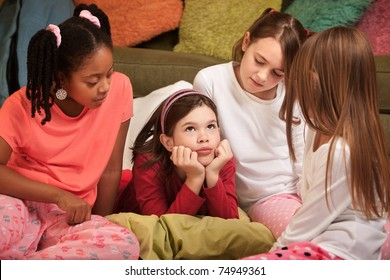 Little girl with hands on chin at a pajama party
