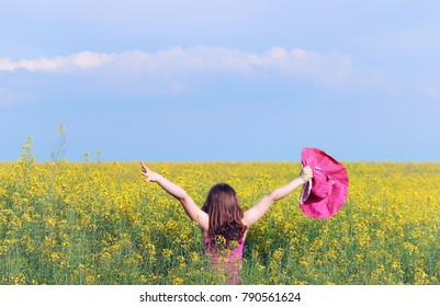 Little girl with hands up on meadow spring season