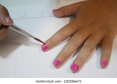 little girl hands painted nails with pink color