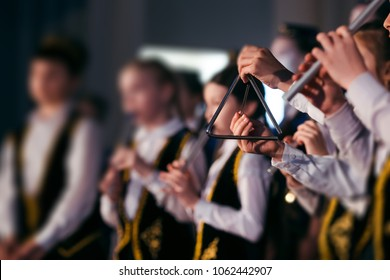 Little girl hands is playing on a musical triangle at stage. Children orchestra in Tatar national clothes and skullcaps plays on the national instrument Kurai