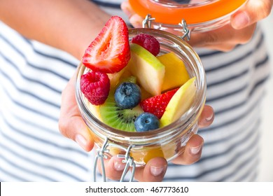 Little girl hands showing a fruit salad on a jar. Healthy snack for children concept
