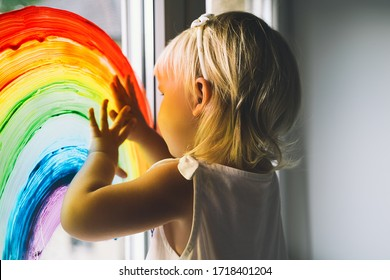 Little girl hands touch painting rainbow on window. Child Art and Creative. Kids leisure at home, childcare, safety joy symbol. Positive visual support during quarantine Coronavirus Covid-19 at home.