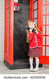 little girl with handset, looking at camera