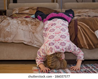 Little girl hanging off the side of a bed balancing her head and hands on the floor as she amuses herself playing