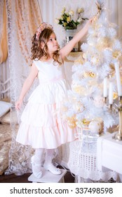 Little girl hangs Christmas decorations on the Christmas tree in her bedroom standing on a chair